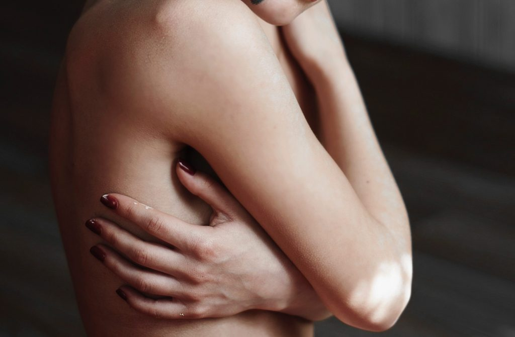 woman with breast implants and doubts on bia-alcl hugging herself